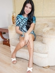 Thick and sexy in all the right places, Ladyboy Nanne is wearing a long blue shirt blouse on a beige couch.