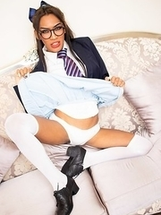 Ladyboy Nutty is in a school girl's outfit complete with a jacket, tie, and glasses.