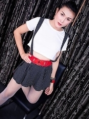 Ladyboy Ice is wearing a skirt with suspender straps over a little white blouse with high heels.