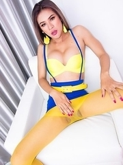 Ladyboy Taan is wearing a yellow bra with a blue skirt with suspenders, white boots, and pantyhose.