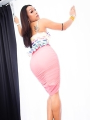 Ladyboy Far poses her curvy body in a corner of the bedroom wearing a white rainbow top and and a hot pink skirt.
